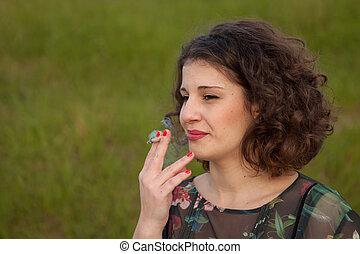 casual, mujer joven, fumar, un, cigarro