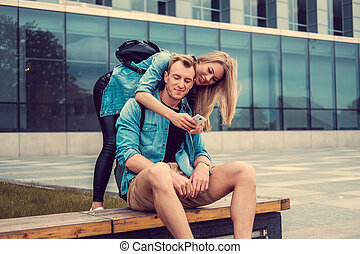 casual, par jovem, usando, smartphone.