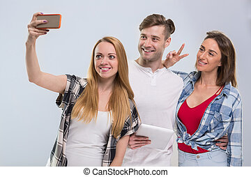 Casual People Group, Young Man Two Woman Happy Smile Taking Selfie Photo Cell Smart Phone Network Communication