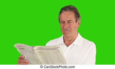 Casual retired man wearing a shirt reading the newspaper