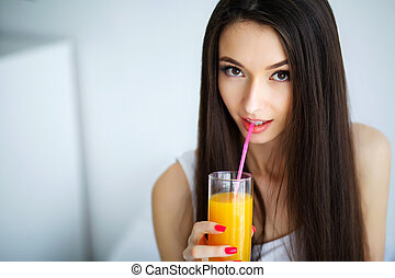 Casual smiling woman holding a glass of orange juice