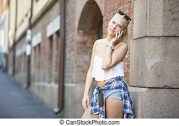 Casual smiling young girl talking in the phone - Pretty and...