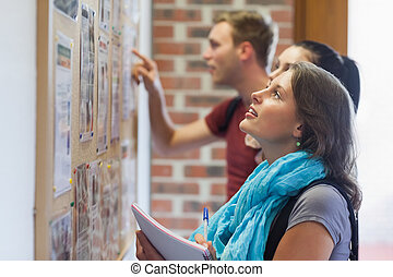 Casual students looking at notice board