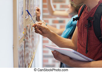 Casual students searching something on notice board