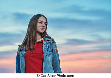 Casual teen girl standing looking away at sunset background
