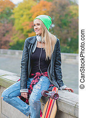 Casual trendy young woman with her skate board