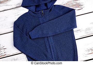 Casual wear hooded knitted sweater. Close up of new folded...