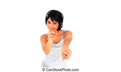 Casual woman dancing with headphones against a white ...