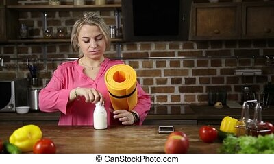 Casual woman getting ready for fitness in kitchen