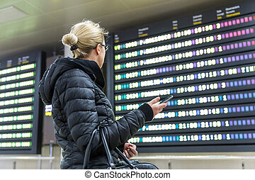 Casual woman in international airport looking at the flight information board.