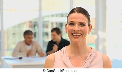 Casual woman looking at the camera with people in the background