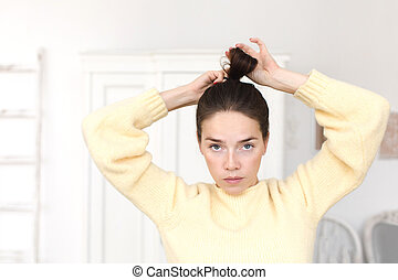Casual woman making hairstyle looking at camera - Serious...
