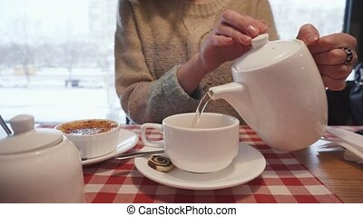 Casual woman pouring organic tea into the ceramic cup.