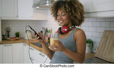 Casual woman relaxing with phone in kitchen - Charming young...