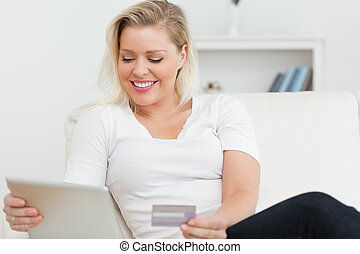 Casual woman sitting on a sofa using a tablet pc