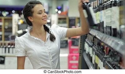 Casual woman taking bottle of wine