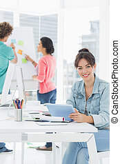 Casual woman using digital tablet with colleagues behind in office