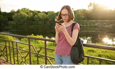 Casual woman using smartphone in the European city, standing outdoors on the bridge.