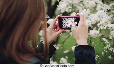 Casual woman with a phone in a blooming spring garden. Back view.