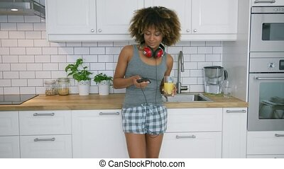 Casual woman with phone drinking juice - Pretty curly woman...
