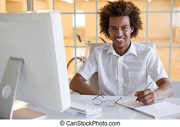 Casual young businessman writing at his desk smiling at camera