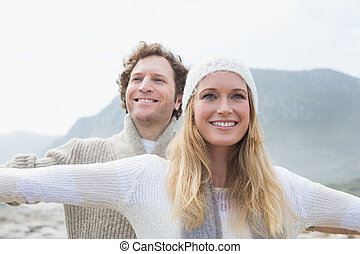 Casual young couple stretching hands out outdoors