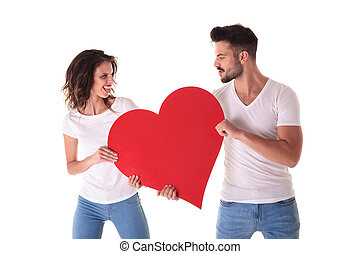 casual young man and woman fighting over a big heart