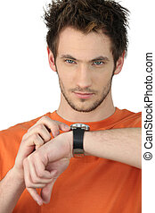 Casual young man checking his wrist watch
