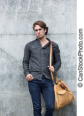 Casual young man standing with bag