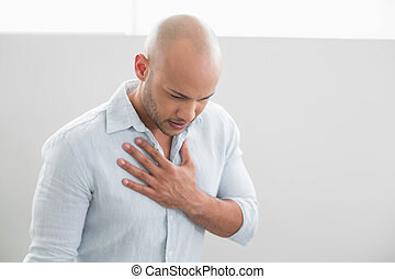 Casual young man with chest pain standing against white...
