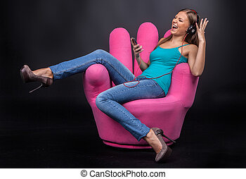 Casual young woman listening to mp3 player. brunette girl sitting in armchair and laughing emotionally
