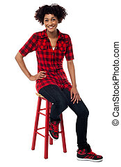 Casual young woman sitting on stool