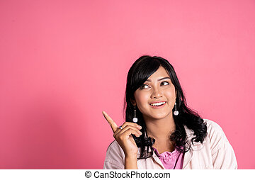 casual young woman thinking and pointing up to copyspace