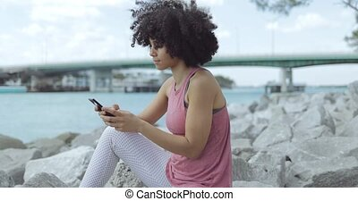 Casual young woman using phone on embankment