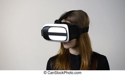 Casual young woman wearing virtual reality goggles moving...