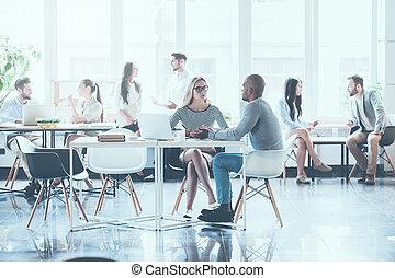 casuale, lavorativo, day., gruppo, di, giovane, persone affari, lavorativo, e, comunicare, con, altro, mentre, seduta, a, loro, lavorativo, locali, in, ufficio