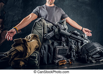 Casually dressed man showing his military uniform and equipment. Modern special forces equipment.