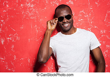 Casually handsome. Cheerful young African man adjusting his sunglasses and smiling while standing against red background