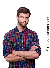 Casually handsome. Portrait of handsome young man in casual shirt keeping arms crossed and looking at camera while standing isolated on white