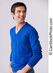 Casually handsome. Side view of handsome young man in blue sweater looking over shoulder and smiling while standing against grey background