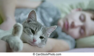 cat and boy teenager indoors sleeping together friendship...