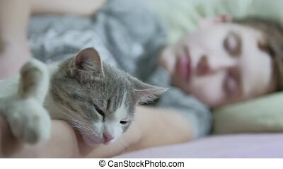 cat and boy teenager sleeping indoors together friendship...