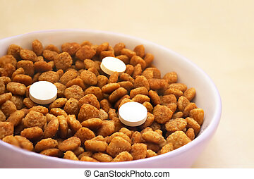 Cat food with three pills in a bowl on the floor. Vitamins for cats. Cat treatment