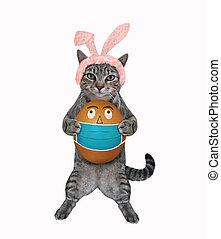 Cat gray holds easter egg in mask