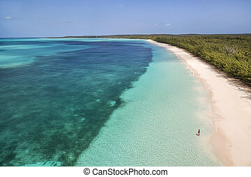 Aerial view of a woman standing along the shoreline and enjoying the views of the turquoise waters and a brilliant pink beach in Cat Island, Bahamas