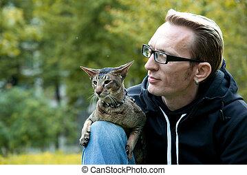 cat sits on the mans lap