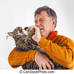 cat trying to catch the glasses of a man