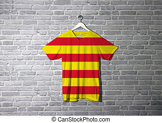 Catalonia flag on shirt and hanging on the wall with brick pattern wallpaper.