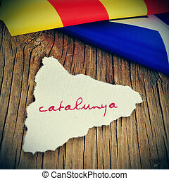 a piece of paper in the shape of Catalonia with the word Catalunya, Catalonia written in catalan, on a wooden background with an estelada flag in the background