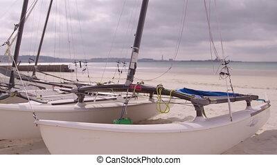 Catamaran moored on a sandy beach - A handheld close up shot...
